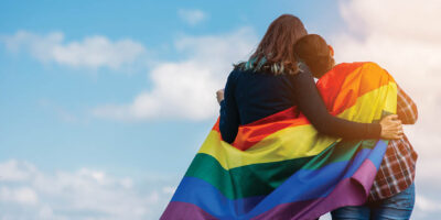Lesbian couple hugging outdoors. LGBT rainbow flag